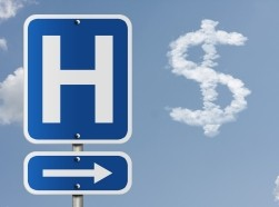 Hospital sign near clouds shaped like a dollar sign, photo by Karen Roach/Adobe Stock