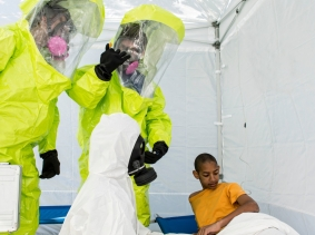 Health workers dressed in hazmat gear and a patient