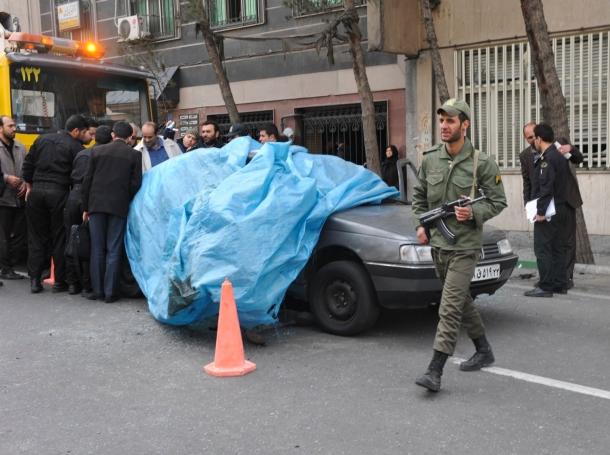 A policeman walks past the car belonging to Iranian nuclear scientist Mostafa Ahmadi-Roshan at a blast site in Tehran, January 11, 2012