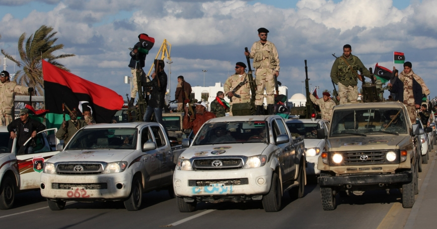 Members of the Libyan military force under the ruling of the National Transitional Council wave their national flag as they parade along a main street in Tripoli February 14, 2012