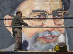 An Iranian worker rests in front of a huge portrait of Iran's Supreme Leader Ayatollah Ali Khamenei on a wall near a university during Friday prayers in Tehran, February 24, 2012