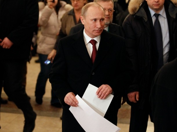 Russian Prime Minister Vladimir Putin walks with his ballot papers before voting in a polling station in Moscow, March 4, 2012
