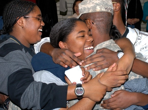 A returning U.S. soldier getting hugged by his family