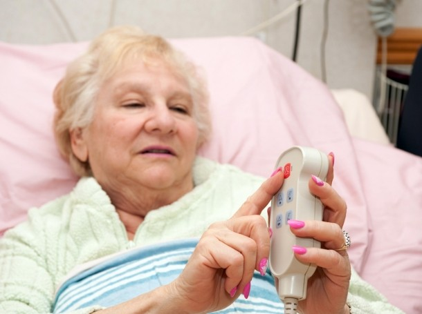 A woman calling a nurse from her hospital bed
