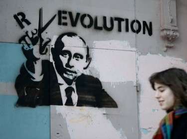 A woman passes by a graffiti displaying Russia's Prime Minister and presidential candidate Vladimir Putin in Moscow, March 3, 2012