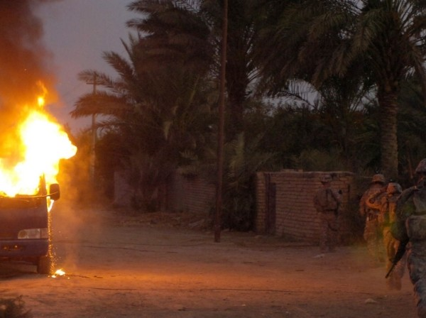 U.S. and Iraqi soldiers run by a burning vehicle in Hussein Hamadi village, Iraq