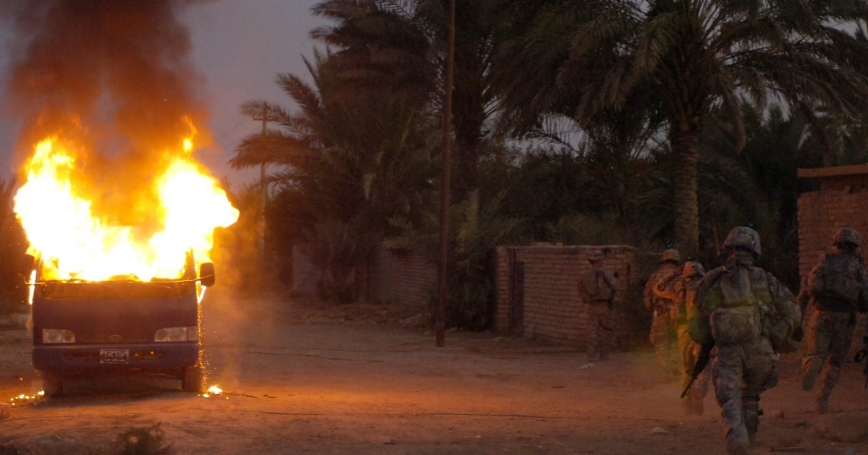 U.S. and Iraqi soldiers run by a burning vehicle in Hussein Hamadi village, Iraq