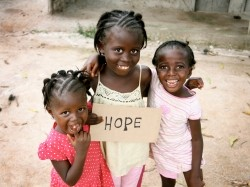 Three girls in Africa holding a HOPE sign
