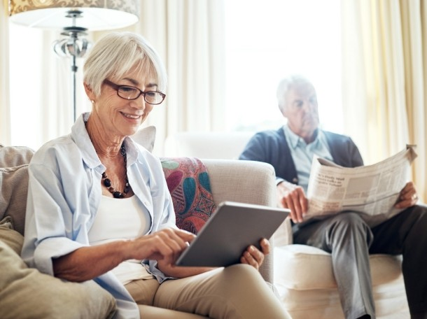 A woman using a digital tablet while her husband reads a newspaper