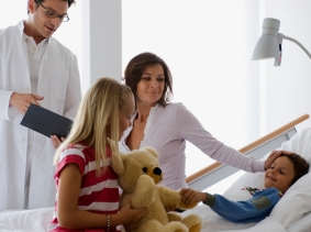 A child in a hospital with family visiting