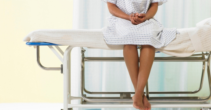 Female patient sitting on a gurney in a hospital