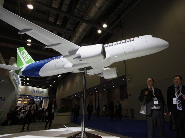 Visitors look at a model of C919 passenger plane during the Asian Aerospace Show in Hong Kong, March 8, 2011