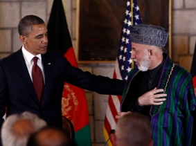 U.S. President Barack Obama puts his arm on Afghan President Hamid Karzai after they signed the Strategic Partnership Agreement in Kabul, May 2, 2012