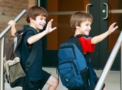 Two boys walking into a school