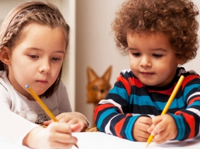 Preschool children drawing with pencils