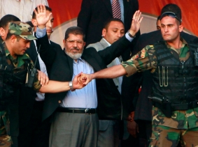 Egypt's Islamist President-elect Mohamed Mursi waves to his supporters while surrounded by members of the presidential guard in Cairo's Tahrir Square, June 29, 2012