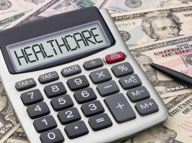 A calculator that says healthcare on top of U.S. currency