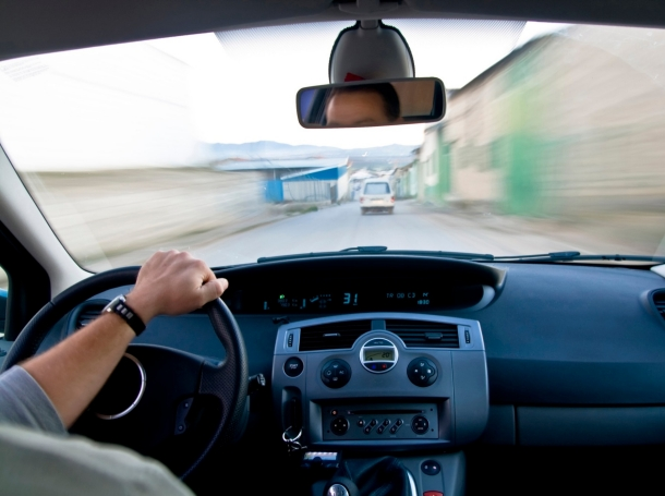 View of a person driving from the back seat of a car