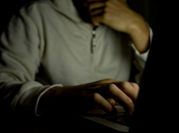 A man on a computer in a dark room