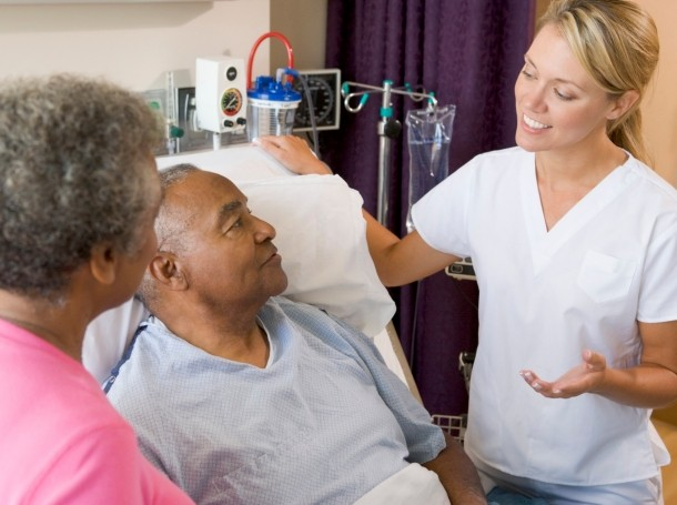A hospital staff member talking to a patient and his wife