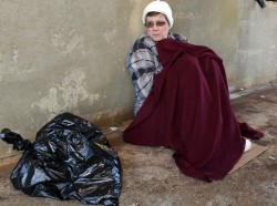 A woman on the street with a blanket and a plastic garbage bag of her belongings