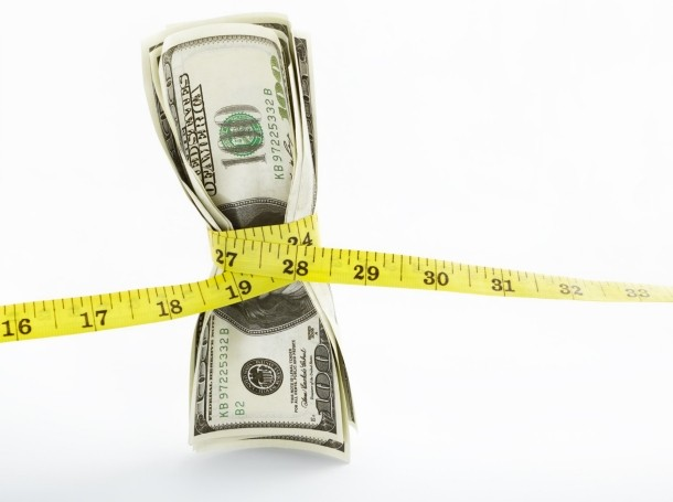 Hundred dollar bills being squeezed by a measuring tape