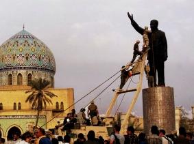 U.S. marines climb up to topple a statue of Iraqi dictator Saddam Hussein at al-Fardous Square in Baghdad, Iraq, April 9, 2003