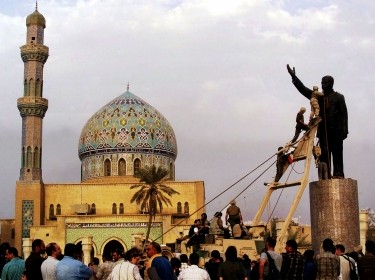 U.S. marines climb up to topple a statue of Iraqi dictator Saddam Hussein at al-Fardous Square in Baghdad, Iraq, April 9, 2003