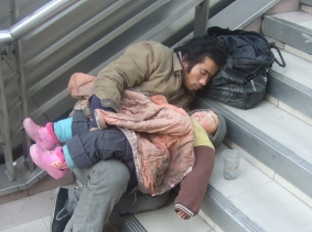 A homeless Chinese man with his daughter sleeping on steps