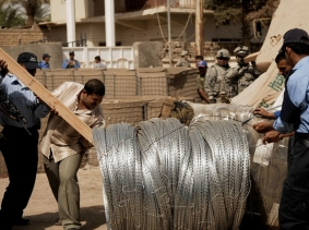 Iraqi police officers and U.S. Army soldiers move reinforcement supplies