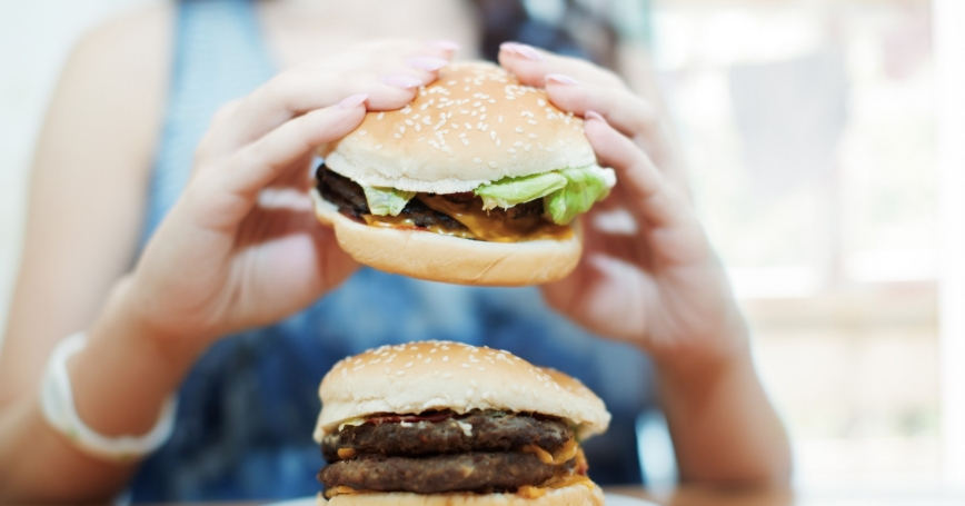 A woman eats a hamburger