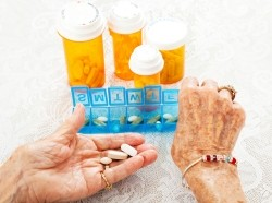 An elderly woman sorting multiple prescriptions