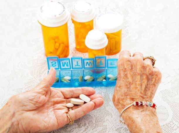 An elderly woman sorting multiple prescriptions