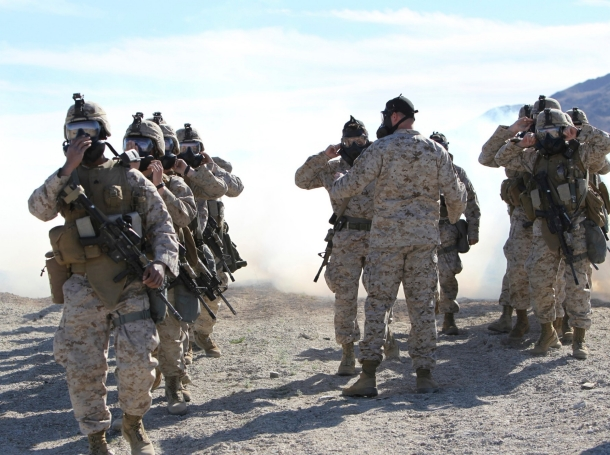 Marines and sailors participate in an outdoor gas exercise in full protective gear