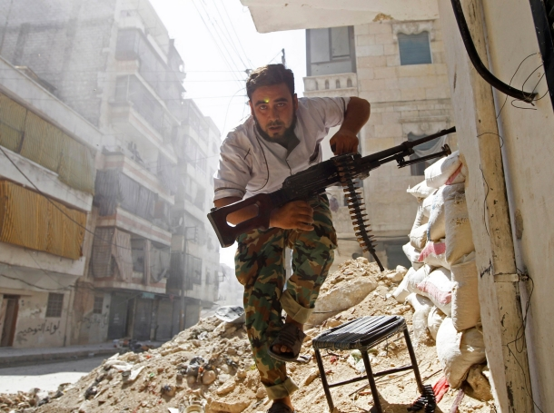 A Free Syrian Army fighter takes cover during clashes with the Syrian Army in the Salaheddine neighbourhood of central Aleppo, August 7, 2012
