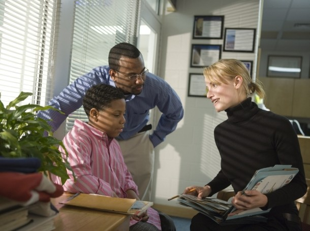 A principal talking to a student and his parent in her office