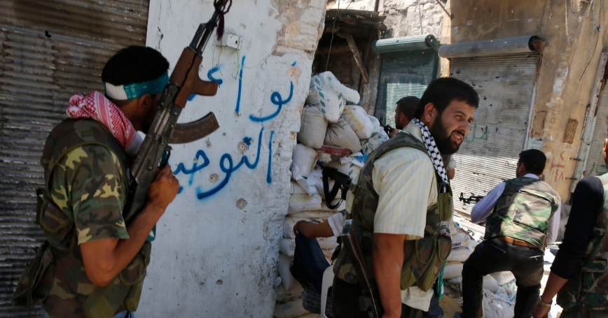 Free Syrian Army fighters take cover in the old city of Aleppo August 27, 2012