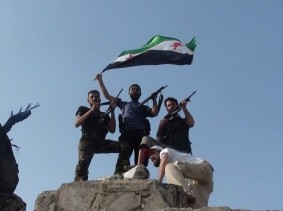 Free Syrian Army members raise an opposition flag on top of a damaged building in Al-Rasten, near Homs, Syria, July 27, 2012