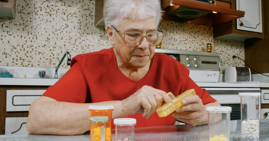 woman at a table with prescription bottles
