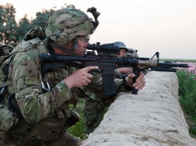 A U.S. Army soldier aims his M4 carbine over a wall in Char Shaka, Kandahar province, Afghanistan