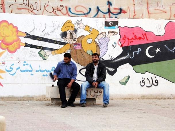 two Libyans sitting in front of Gaddafi graffiti