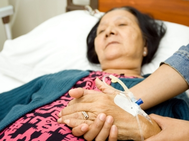 patient in hospital bed with family member visiting