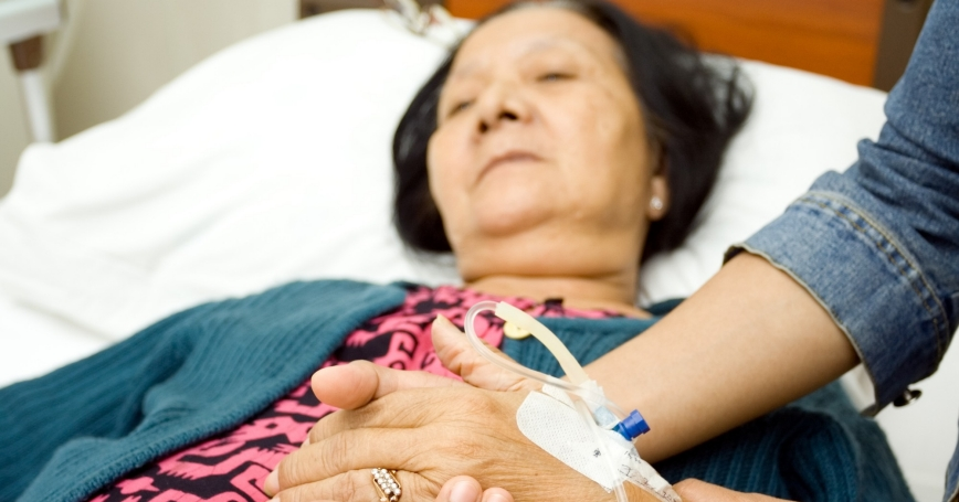 patient in a hospital bed with a family member by her side