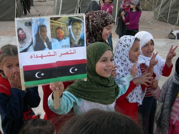 Libyan children at a refugee camp hold up a sign with revolutionary slogans