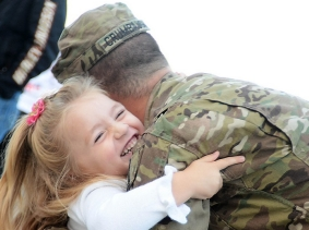 a soldier is welcomed home by his daughter after a year long tour in Afghanistan