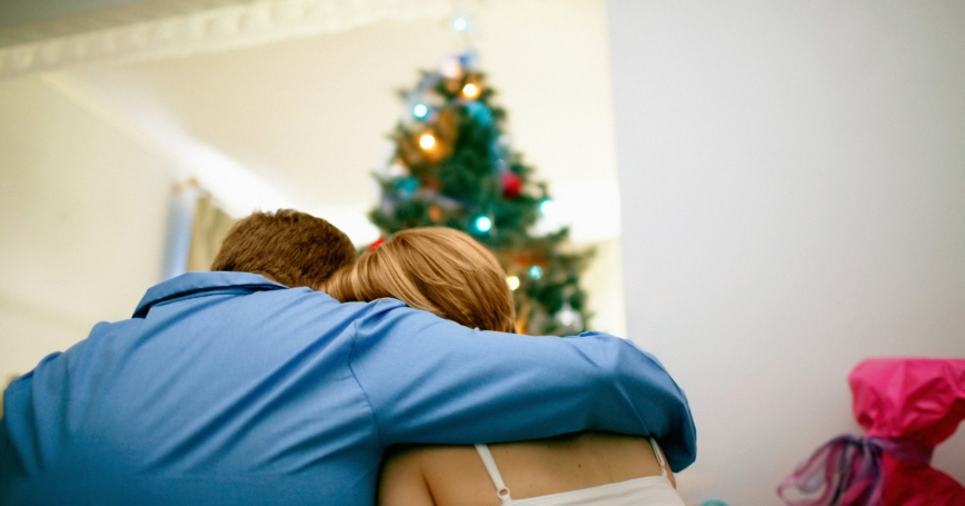 couple consoling each other in front of a Christmas tree