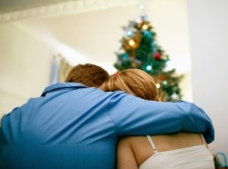 couple consoling each other in front of Christmas tree