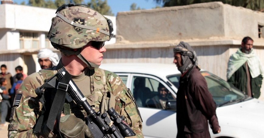 U.S. Army soldier and security force team member maintains security on the street during a key leader engagement in the Lash-e Juwayn district of Farah province, Afghanistan