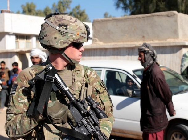 U.S. Army soldier and security force team member maintains security on the street during a key leader engagement in the Lash-e Juwayn district of Farah province, Afghanistan.