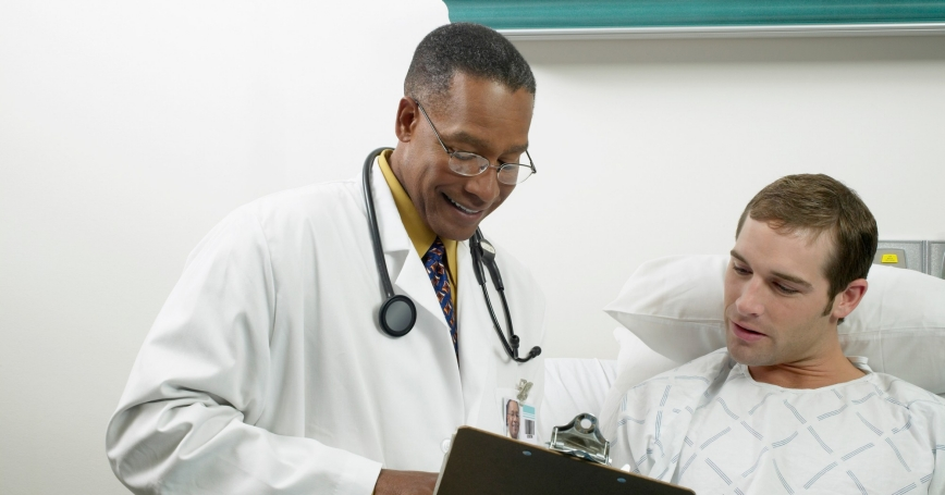 doctor holding a clipboard talking to a patient